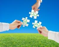 Le mani tengono i puzzle con riciclano il simbolo ed il bello paesaggio g Fotografia Stock Libera da Diritti