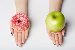 Le mani tengono la ciambella e la mela su fondo bianco Fotografia Stock
