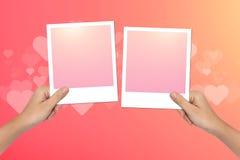 Le mani tengono la struttura in bianco della foto sul fondo rosa del giorno di biglietti di S. Valentino Fotografie Stock Libere da Diritti