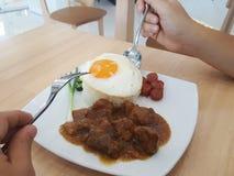 Le mani umane portano il cucchiaio e la forchetta per mangiare l'alimento asiatico che è riso con l'uovo fritto, la salsiccia di  immagine stock