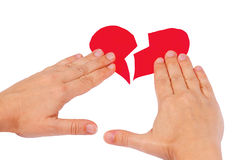 Le mani uniscono il cuore rosso rotto Fotografia Stock