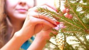 Le mani vicine appendono il cono del giocattolo del pino sul movimento lento dell'albero del nuovo anno archivi video
