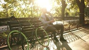 Le mannen i den blåa skjortan som sittting på bänken och talar på hans mobiltelefon Att ta för ryttare vilar, når det har cyklat  lager videofilmer