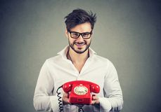 Le mannen i den vita skjortan och exponeringsglas som rymmer den röda telefonen som arbetar för kundtjänst royaltyfri foto