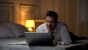 Le mannen i den vita skjortan på säng som ler och pratar på bärbara datorn, kontorsangelägenhet fotografering för bildbyråer