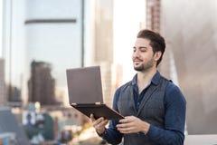 Le mannen i en affärsdräkt som arbetar på hans bärbar dator med en friare royaltyfria foton