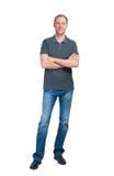 Le mannen i grå t-skjorta och jeanse som isoleras på den vita backgroen arkivfoto