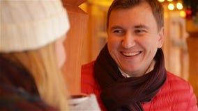 Le mannen i rött omslag och rödbruna halsduken som har den varma drinken och talar med kvinnan om något som är rolig lyckliga par stock video