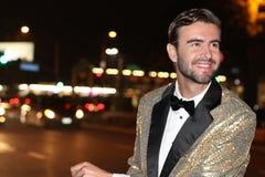 Le mannen i sparkly guld- le för smoking Arkivbilder