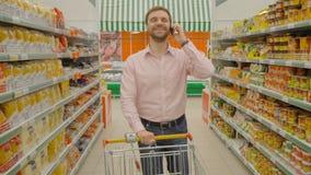 Le mannen köp mat och att ringa på supermatket stock video