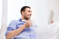 Le mannen med den minnestavlaPC och koppen hemma Fotografering för Bildbyråer