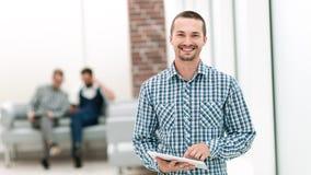 Le mannen med ett digitalt minnestavlaanseende i kontoret arkivfoto