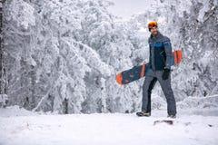 Le mannen med skida maskeringen som rymmer hans snowboard, extrem sport a Royaltyfri Foto