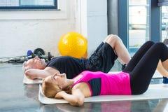 Le mannen och kvinnan i sportswearen som gör abs i idrottshall Arkivbilder