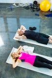 Le mannen och kvinnan i sportswearen som gör abs i idrottshall Royaltyfri Bild