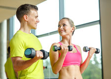 Le mannen och kvinnan med hantlar i idrottshall Royaltyfria Bilder