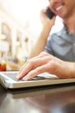 Le mannen på påringningen som arbetar på bärbara datorn royaltyfria bilder