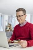 Le mannen som använder kreditkorten och bärbara datorn för att shoppa direktanslutet hemma under jul Fotografering för Bildbyråer