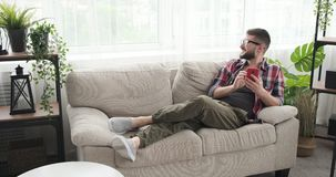 Le mannen som anv?nder mobiltelefonen p? soffan stock video