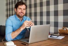 Le mannen som direktanslutet arbetar och hemma dricker kaffe Royaltyfria Bilder