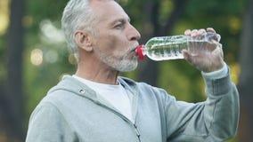 Le mannen som dricker den buteljerade drycken som håller vattenjämvikt efter genomkörare stock video