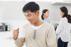Le mannen som dricker kaffe med familjen i bakgrund Royaltyfria Bilder