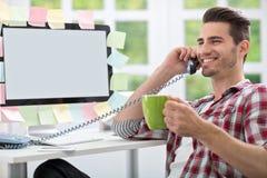 Le mannen som dricker kaffe på kontoret Arkivfoton