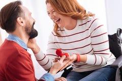 Le mannen som gör ett förslag till en nöjd rörelsehindrad kvinna Arkivbild