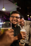 Le mannen som har öl med hans vänner i en bar arkivbild