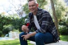 Le mannen som har exponeringsglas av rött vin i trädgård Fotografering för Bildbyråer
