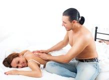 Le mannen som masserar det behind av hans kvinna Royaltyfri Fotografi