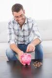 Le mannen som sätter mynt i en spargris Royaltyfria Bilder