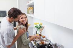 Le mannen som ser hans fru som lagar mat grönsaker royaltyfria bilder