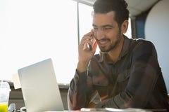 Le mannen som talar på telefonen på kontoret Fotografering för Bildbyråer