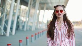 Le mannequin dans des lunettes de soleil rouges marche sûr le long de la rue près du centre commercial Jeunes adultes clips vidéos
