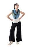 Le mannequin de cheveux courts avec le châle coloré et desserrent les pantalons larges posant avec des bras sur ses hanches Photos stock