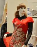 Le mannequin féminin s'est habillé dans l'habillement traditionnel chinois rouge avec le modèle de Phoenix dans un magasin d'habi Photos stock