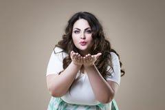 Le mannequin plus de taille envoie le baiser d'air, grosse femme sur le fond beige, corps féminin de poids excessif Photographie stock