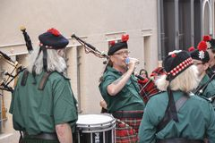 LE MANS, ΓΑΛΛΙΑ - 13 ΙΟΥΝΊΟΥ 2014: Η σκωτσέζικη ζώνη bagpipe βαδίζει κάτω από την οδό κατά τη διάρκεια της παρέλασης του αγώνα πι Στοκ Εικόνες
