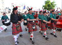 LE MANS, FRANCE - JUNE 13, 2014: Scottish bagpipe band is marching down the street during parade of pilots racing. Stock Photo