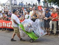 LE MANS, FRANCE - JUNE 16, 2017: Worker Man Collecting Garbage with cans and plastic on the street at parade of pilots. LE MANS, FRANCE - JUNE 16, 2017: Worker Stock Photo