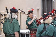 LE MANS FRANKRIKE - JUNI 13, 2014: Den skotska säckpipe- musikbandet marscherar ner gatan under ståtar av att springa för piloter Arkivbilder