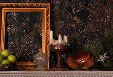 Le manteau de cheminée avec le cadre, les pommes, les gâteaux, le chandelier et le pin s'embranchent Photographie stock