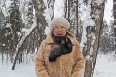 Le manteau de fourrure et le chapeau de vieille dame se tenant dans la neige froide d'hiver ont couvert la forêt Photographie stock