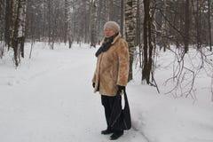 Le manteau de fourrure supérieur et le chapeau de femme se tenant dans la neige froide d'hiver ont couvert la forêt Photographie stock libre de droits