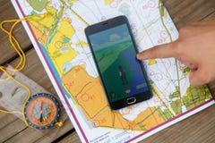 Le mappe, i compas e la manifestazione della mano per telefonare lo schermo con Pokemon vanno l'applicazione fotografia stock libera da diritti