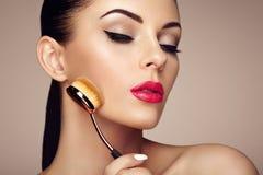 Le maquilleur applique le skintone avec la brosse Photographie stock libre de droits