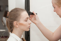 Le maquilleur appliquent la jeune fille de maquillage avant le photoshoot Image libre de droits