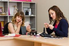 Le maquilleur consultera des cosmétiques Photo libre de droits