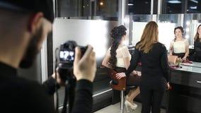 Le maquilleur fait un maquillage à la fille aux cheveux foncés banque de vidéos